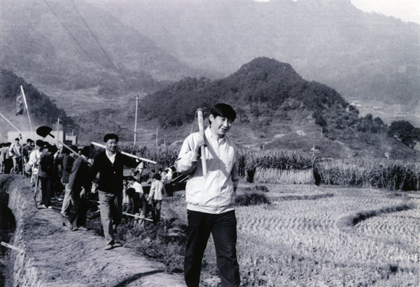 File photo taken in 1988 shows Xi Jinping (front), then secretary of the Ningde Prefecture Committee of the Communist Party of China (CPC), participates in farm work during his investigation in the countryside. (Xinhua)