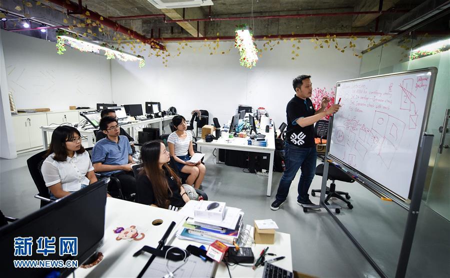 10月14日,谢智衡(右一)召集员工开会讨论技术问题.